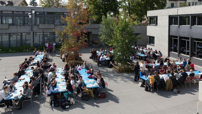 Studierende draussen an Tischen vor der Mensa der Universitaet St.Gallen (HSG)